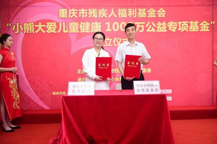 重庆市残疾人福利基金会理事长郝建新先生(右)与重庆小米熊儿童医院院长谭秋女士(左)展示刚刚签订的合作协议.jpg