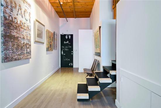 过道的砖瓦墙是loft风格的标志性装饰。进门的地方放上两个座椅,方便换鞋。黑白交错的楼梯打造出层次分明的 ...